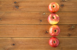 fruits, food and harvest concept - ripe red apples on wooden table