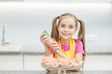 Smiling Little Girl With Confectionery Bag Squeezing  Cream On Cupcakes. Empty Space For Text