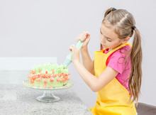 Little Girl Decorating Cake In The Kitchen At Home