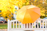 season, rainy weather and people concept - woman with umbrella sitting on bench in autumn park - 275442927