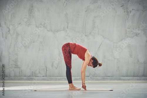 Side view of beautiful Caucasian brunette in red sports wear standing barefoot on the mat in Standing Forward Bend yoga posture Canvas Print