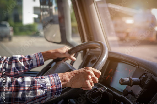 Obraz Truck driver keeps driving with one hands and change gears,The man Behind Semi Truck Steering Wheel,spot focus. - fototapety do salonu