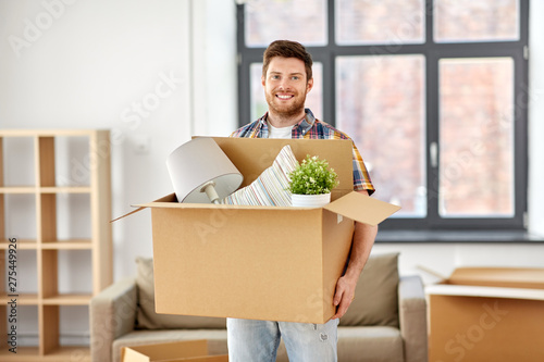 moving, people and real estate concept - happy man with boxes at new home - 275449926