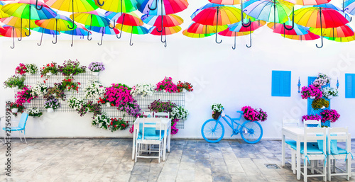 Charming street (outdoor) decoration with old bicycle , flowers and umbrellas. Bodrum, Turkey