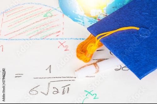 Graduation cap on paper math formula equation graph and blur of