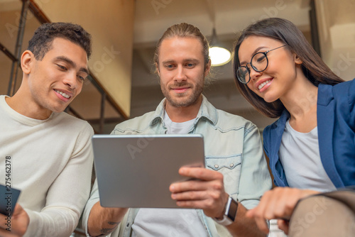 Fototapety, obrazy: Close up shot of multiracial business people with digital tablet having meeting in office. Business people looking at tablet computer and smiling