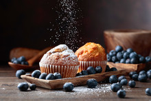Muffins And Blueberries Sprinkled With Powdered Sugar.