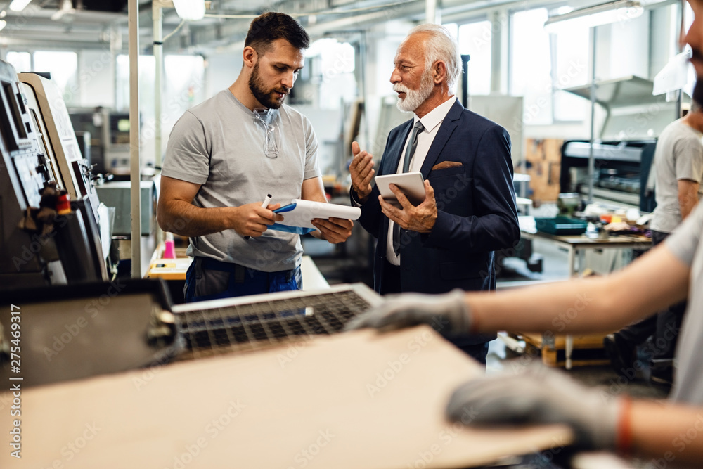 Fototapety, obrazy: Senior engineer communicating with young worker while visiting industrial facility.