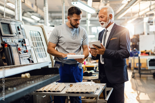Smiling mature engineer and worker using touchpad in factory plant.