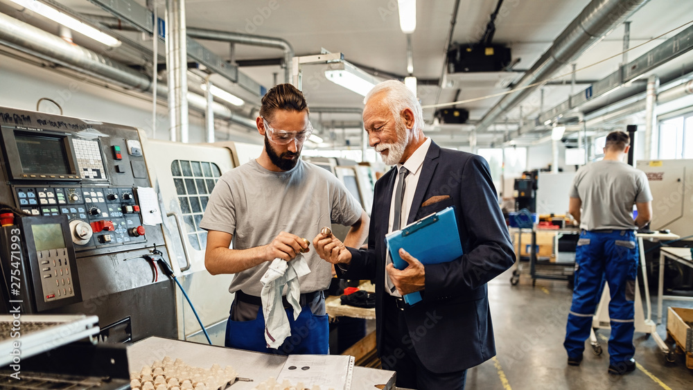 Photo  Mature engineer and manual worker examining quality of manufactured components in a factory
