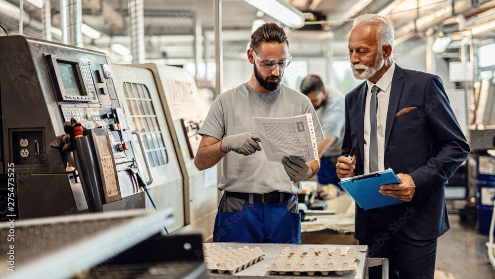 Fototapety, obrazy: Mature company manager and worker going through reports in industrial facility.