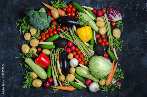 Fotobehang top view portrait of Assortment of fresh raw vegetables on black wooden background.