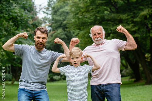 Carta da parati  Portrait og happy family - grandpa, father and his son smiling and showing their muscles outdoor in park on background