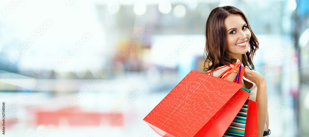 Fototapeta Picture of happy beautiful girl with color shopping bags, at mall
