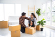 Asian couple family husband and wife packing box moving in new house or unbox for shopping online business living room with white color and sofa