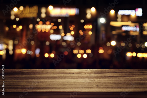 Fotografía  background of wooden table in front of abstract blurred restaurant lights
