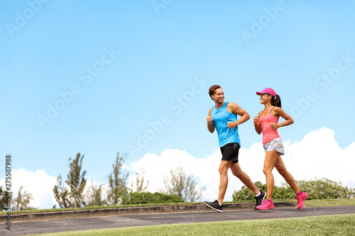 Photo Stands Height scale Runners athlete fit people running on street - summer active lifestyle fitness couple training outdoors.