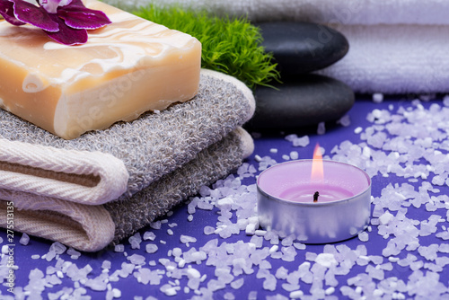 Spa Wellness Concept. Natural Back Scrubber,Goat milk Soap, Basalt Stones, Orchid, Dianthus Flower and Lavender Tea Light Candle on purple background.