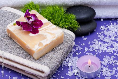 Spa Wellness Concept. Natural Back Scrubber,Goat milk Soap, Basalt Stones, Orchid, Dianthus Flower and Lavender Tea Light Candle on purple background.