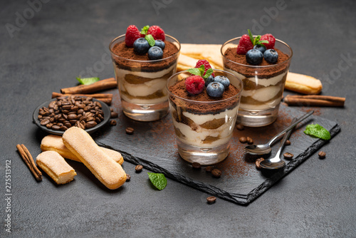Foto auf Leinwand Bekannte Orte in Asien Classic tiramisu dessert with blueberries and raspberries in a glass and savoiardi cookies on stone serving board on dark concrete background