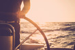 Close up of man's hand on sail boat helm - marine ship lifestyle concept of travel for beautiful holiday destination - alternative people life - sunset and sunlight in background on the ocean
