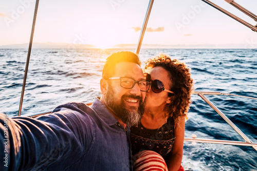 Romantic and happy people caucasian couple kissing and taking selfie on a sail boat - luxury and joyful lifestyle for cheerful adults man and woman together with love and relationship - sunset