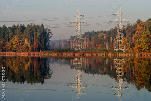 Power line in the cleared area of the forest. Steel electro masts with wires by the lake.