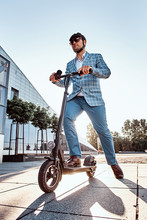 Low Angle Photo Of Smart Elegant Man In Sunglasses And Helmet Which Is Driving His Electrical Scooter.