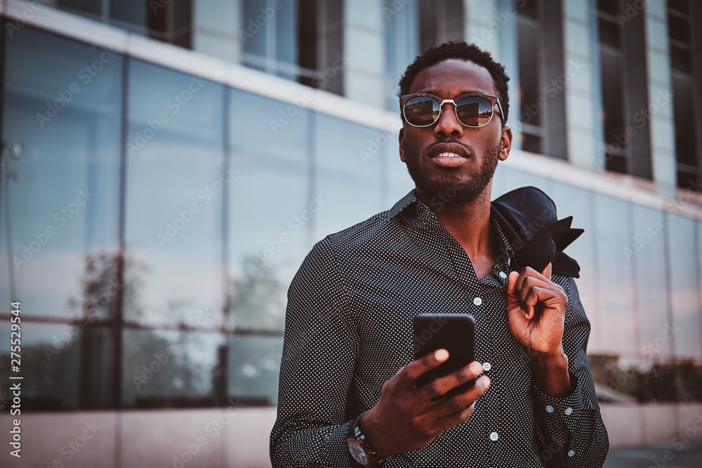 Fototapety, obrazy: Portrait of pensive modern afro man with sunglasses and mobile phone over glass building background.