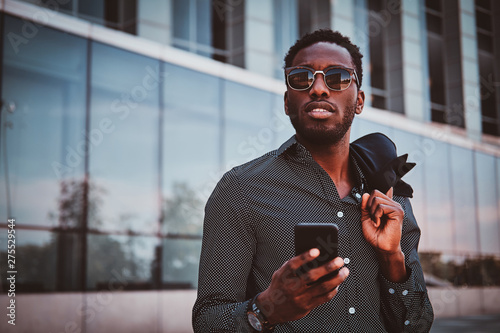 plakat Portrait of pensive modern afro man with sunglasses and mobile phone over glass building background.
