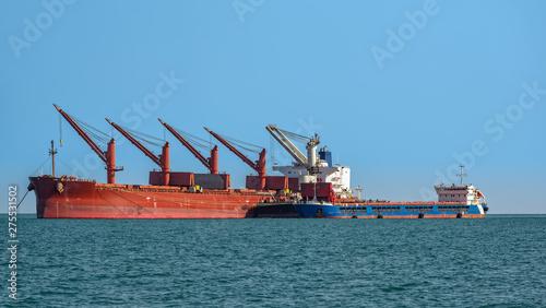 Photo Loading ocean-going bulk carrier ship with Bauxite aluminum ore from the mini bulk carrier (feeder) vessel at offshore Kamsar port, Guinea, West Africa