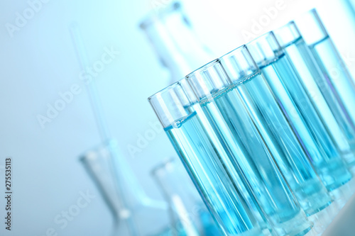 Stampa su Tela  Test tubes with liquid on blurred background, closeup with space for text