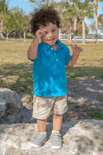 A Toddler Stands Upon A Large Boulder At The Local Park. The Summer Sun Dapples Through The Trees On Him As He Tries To Cover His Eyes And Smiles At The Camera.