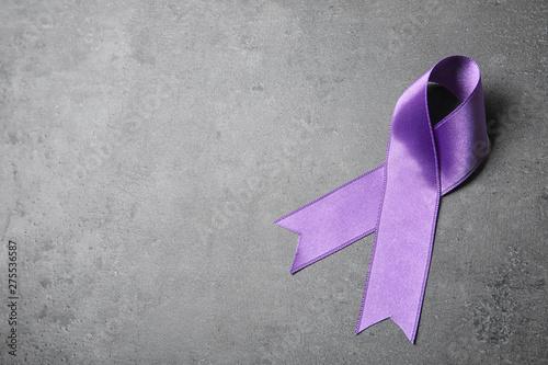 Purple ribbon on grey stone background, space for text Fototapeta