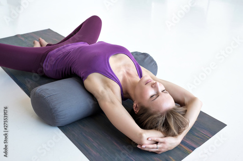 Canvas European slim woman practicing yoga lying in Reclined Butterfly exercise relaxin