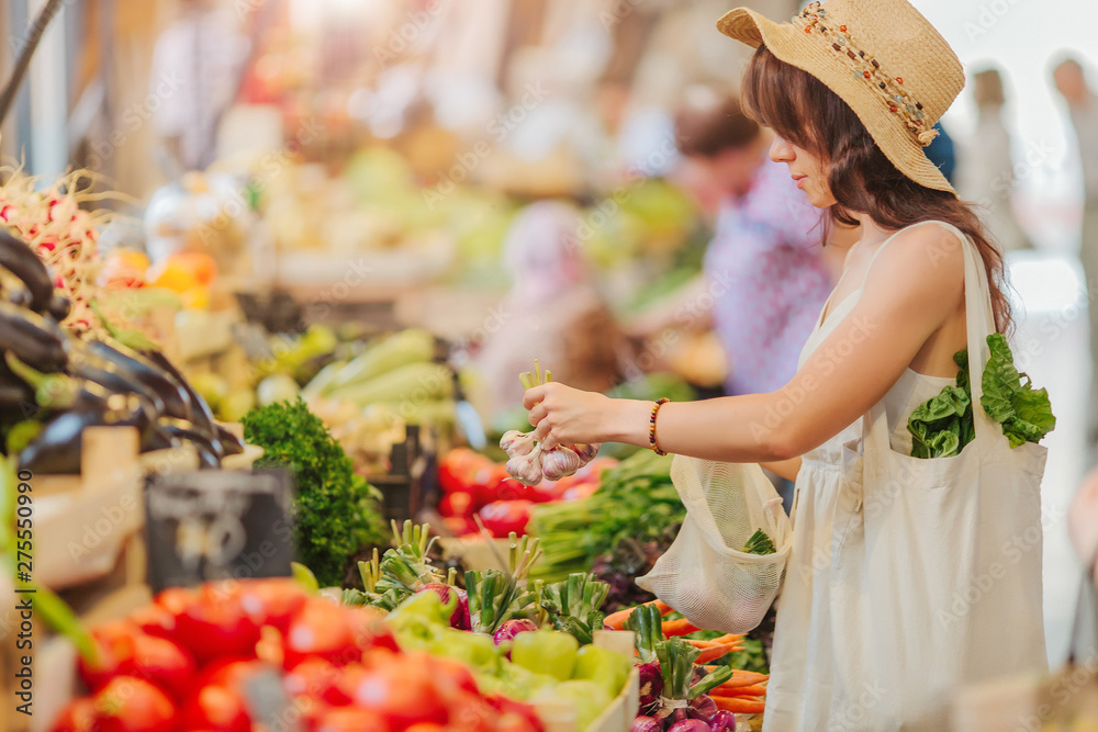 Fototapety, obrazy: Woman is chooses  fruits and vegetables at food market. Reusable eco bag for shopping. Zero waste concept.