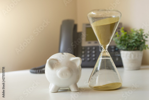 Hourglass with piggy bank on the background with a phone, concept of losing mone Tablou Canvas