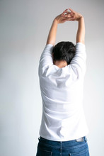 Back Of Woman Stretching Arms Over Head For Stretch Muscle And Exercise.