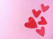 Many Red Heart Made From Plasticine Clay On Pink Background, Cute Shaped Dough