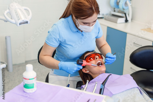 Canvas Dentist working with patient in modern clinic