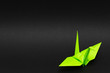 light green origami paper crane on black background