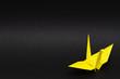 yellow origami paper crane on black background