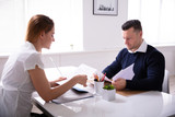 Businesspeople Looking At Document While Interview