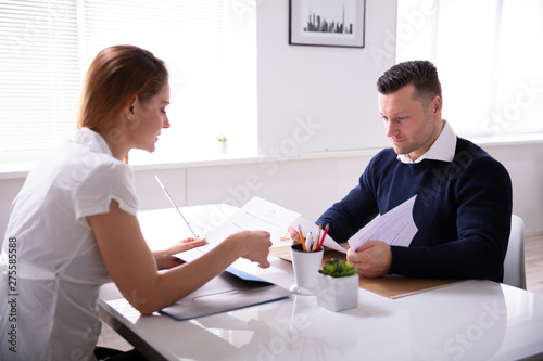 Businesspeople Looking At Document While Interview - 275585588