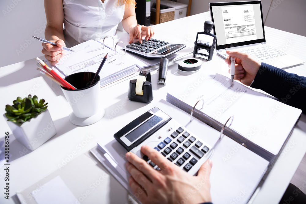 Fototapety, obrazy: Businesspeople Calculating Invoice With Calculator