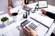 Leinwandbild Motiv Businesspeople Calculating Invoice With Calculator