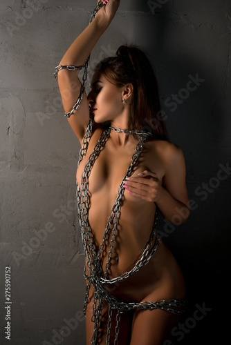 Nude woman wrapped with chain shot