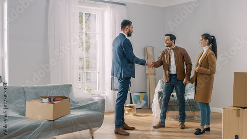Real Estate Agent Shows Bright New Apartment to a Young Couple Canvas Print