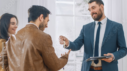 Professional Real Estate Agent in Bright New Apartment Gives Keys to a Young Couple Wallpaper Mural