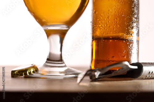 Poster Pierre, Sable Beer glass and bottle on table with bottle opener isolated